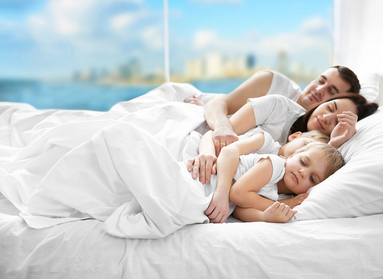 Familie liegt in frisch bezogenem Bett