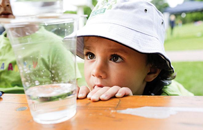 Junge mit Hut schaut sich ein Wasserglas an