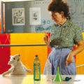 Eine Frau unterhält sich mit einer Schafspuppe über Ballonfahrt