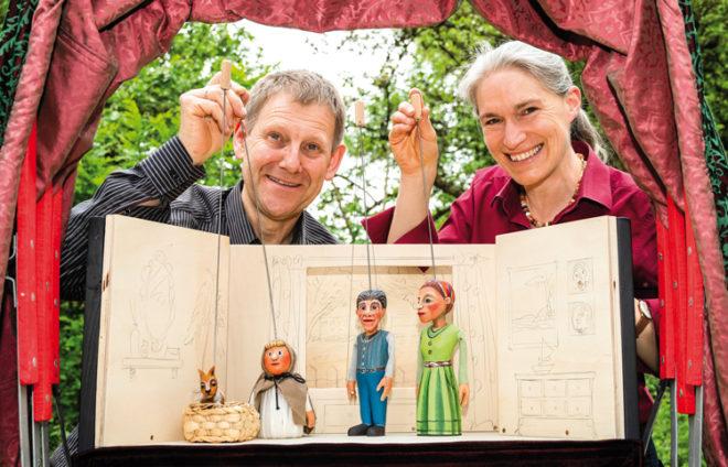 Puppenspieler mit Puppen unter einem roten Vorhang