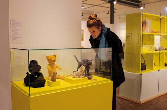 Besucherin schaut sich einen Teddybär an