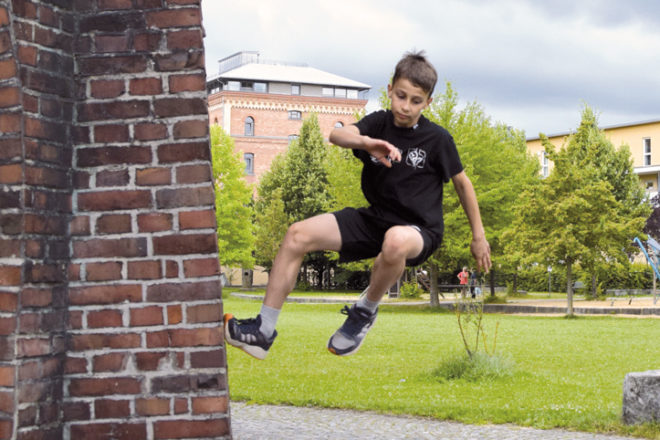 Kind springt von einer Mauer weg