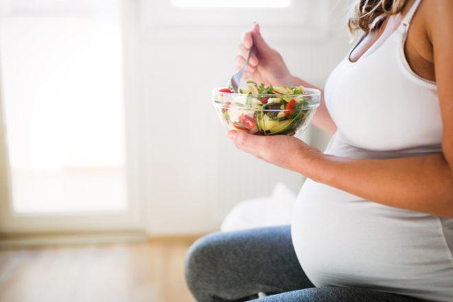 Schwangere Frau mit einer Salatschüssel in der Hand