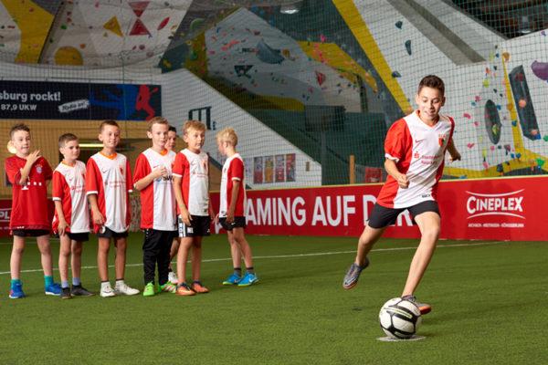 Fußballkind kickt gleich den Fußball, seine Gruppe schaut zu