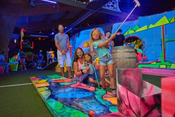 Kind schwingt Minigolfschläger in Neongolf