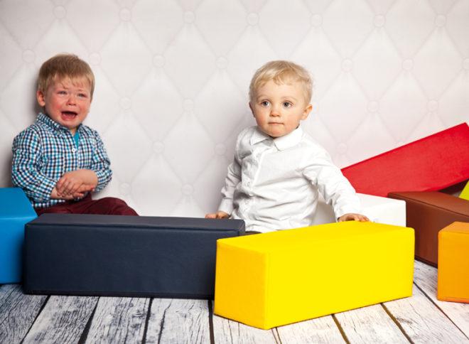 Ein Kleinkind weint, das andere schaut unschuldig