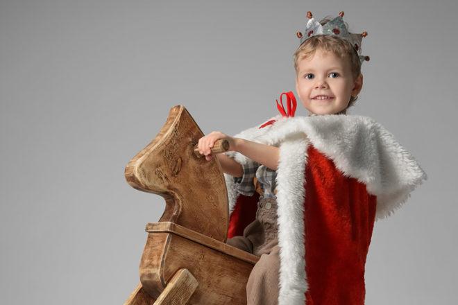 Kind als König auf einem Holzpferd