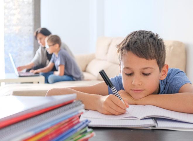 Junge macht lustlos Hausaufgabe, im Hintergrund ein Elternteil mit einem Kind am Laptop