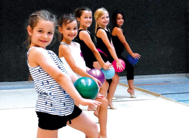 Eine Gruppe Mädchen mit ihren Bällen in einer Sporthalle