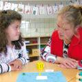 Eine Frau bringt einer Schülerin etwas bei