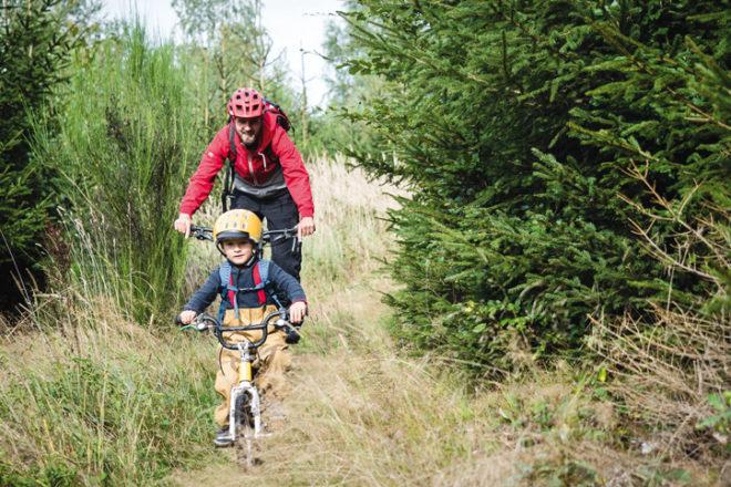Vater und Kind im Wald mit dem Rad unterwegs