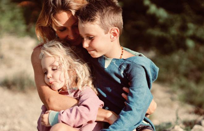 Eine Mutter umarmt ihre Kinder