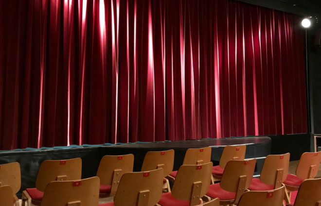 Leere Bühne mit rotem Vorhang und leeren Stuhlreihen