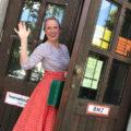 Fräulein Tönchen steht winkend an einem Eingang