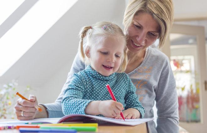 Ein Mädchen sitzt auf dem Schoß ihrer Mutter, sie malt etwas in ein Heft