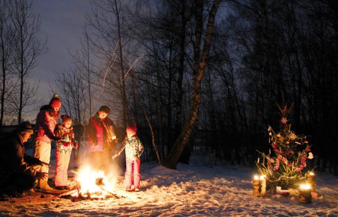 Eine Familie wärmt sich an einer Feuerstelle im Wald