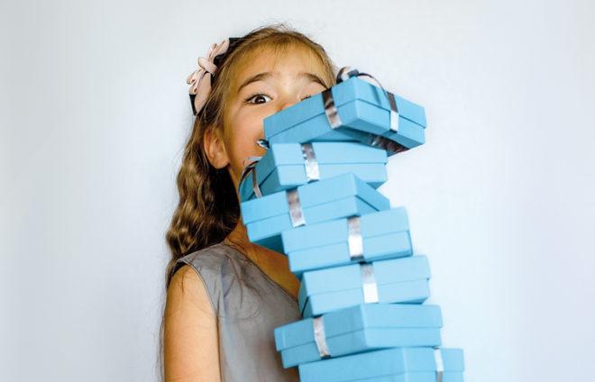 Mädchen mit einem Turm voller Geschenke