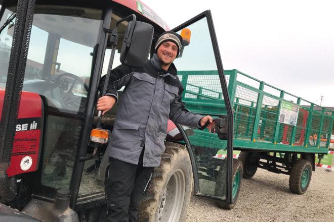 Mitarbeiter vom Tannenhof steht am Traktor