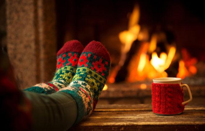 Füße in bunten Wollsocken auf einem Tisch vor einem Kamin