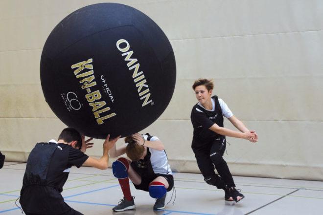 Zwei Jungs halten einen Kin-Ball hoch, ein anderer nimmt Anlauf zum Schlagen