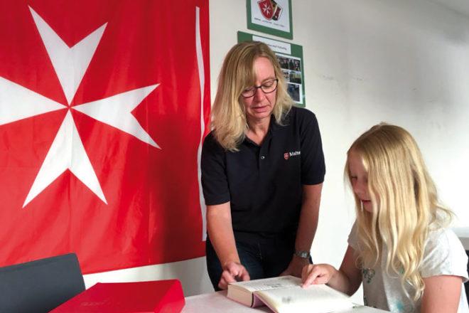 Eine Frau von Malteser hilft einem Mädchen beim Lesen