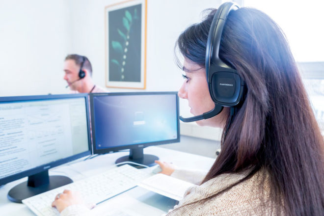 Frau mit Headset am Computer