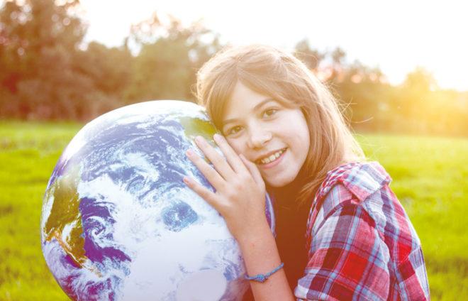 Eine Jugendliche hält die Welt in ihren Händen