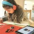 Schülerin mit Kopfhörern macht ihre Hausaufgaben