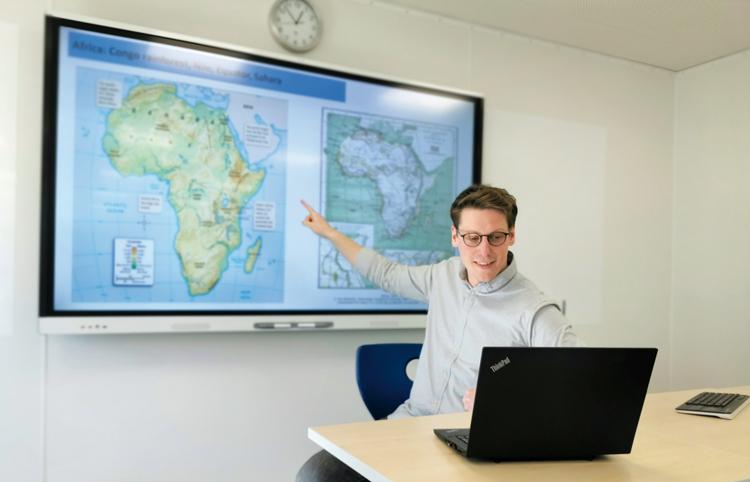 Lehrer zeigt auf einen Bildschirm mit einer angezeigten Karte von Afrika