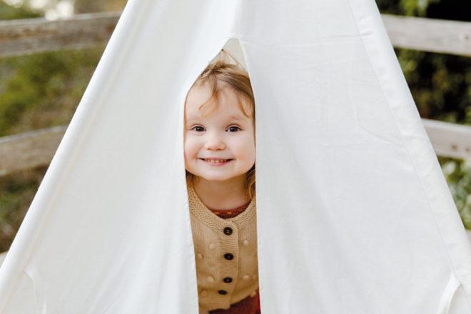 Kind schaut aus einem weißen kleinen Zelt heraus