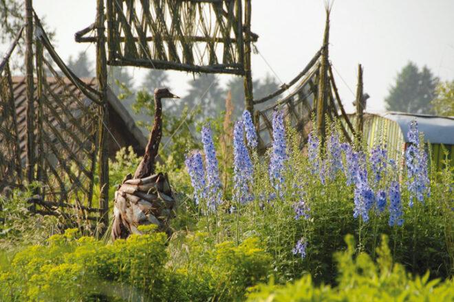 Grüner Garten mit Vogelstrauß aus Holz
