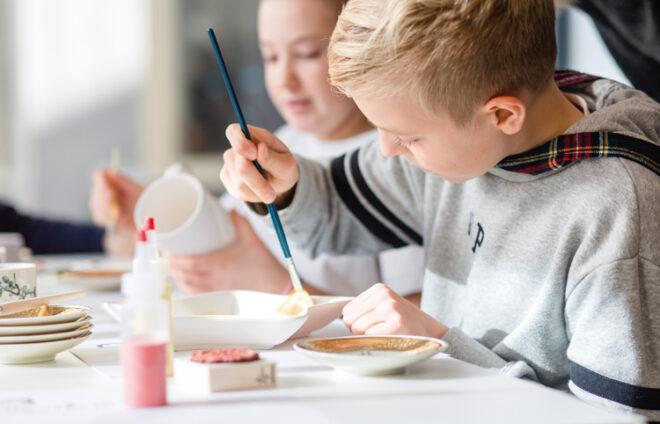 Kind malt Keramikteller an