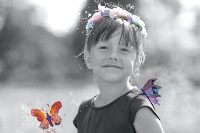 Monochromes Foto eines Mädchens mit bunten Schmetterlingen