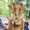 Kinder stehen an geschnitzter Figur von Grüffelo