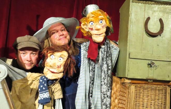 Schauspieler mit ihren Puppen spielen die Abenteuer des Tom Sawyer